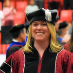 Female doctoral student smiling during WSU Tri-Cities commencement ceremony