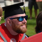 Student smiling big while wearing cool sunglasses after graduating at WSU Tri-Cities