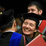 Student happily receivng congratulatory hug from faculty at WSU Tri-City commencement ceremony