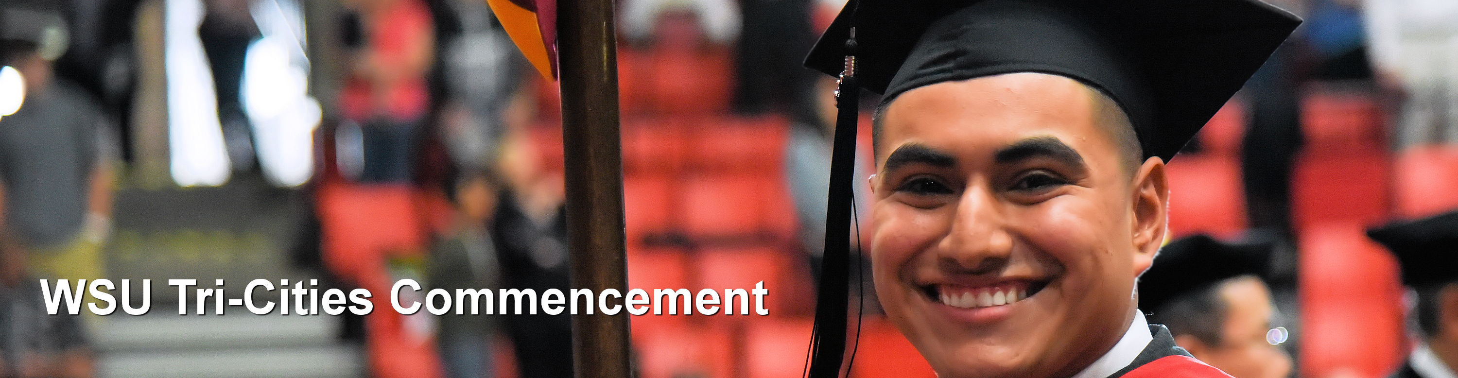 Male student wearing black cap and gown smiling big after recently graduating from WSU Tri-Cities