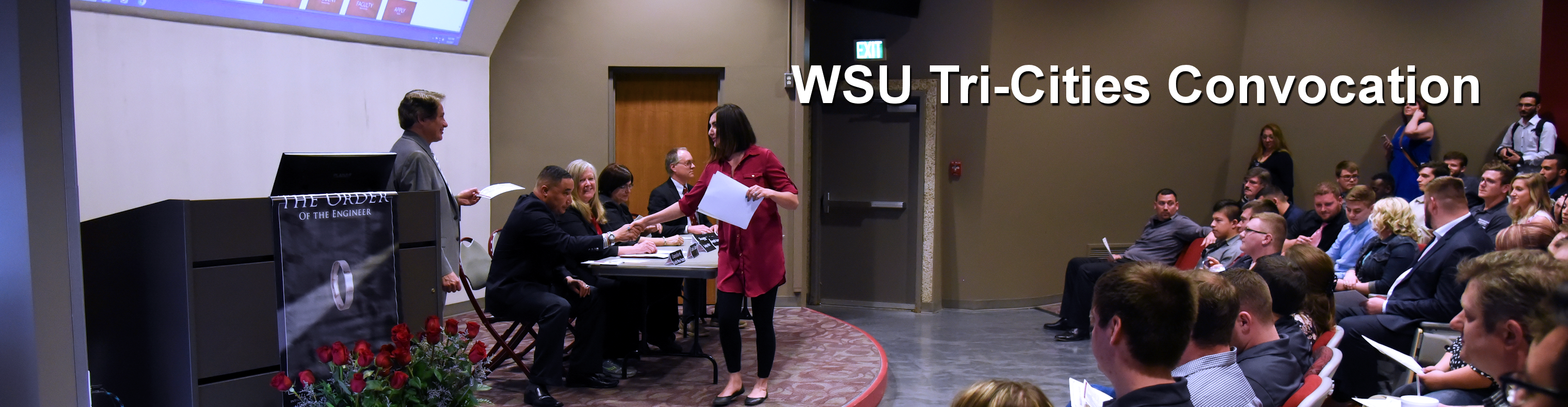 Graduating female student receiving a certificate from the Chancellor during the Order of the Engineer Induction Ceremony at the annual WSU Tri-Cities Convocation ceremony