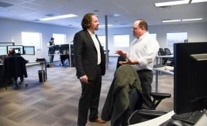 Photo of elevate founder Paul Carlisle talking with a colleague.