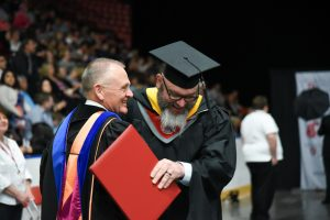 WSU Tri-Cities alumnus Geoff Schramm hugs environmental science mentor Dick Pratt after being hooded at the WSU Tri-Cities commencement ceremony