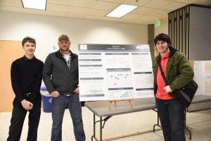 Computer science students post with their project poster during the undergraduate research symposium