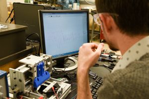 WSU Tri-Cities alumnus Josef Christ observes the electrical signals from a 3D-printed sensor made from nanomaterials as it is stretched