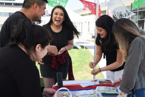 Maria Fernanda Vargas (center) celebrates while playing a game as part of a World Fair offered by student clubs at WSU Tri-Cities