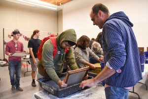 Peace Paper Project founder Drew Matott works with students in an art class at WSU Tri-Cities to create paper from articles of clothing