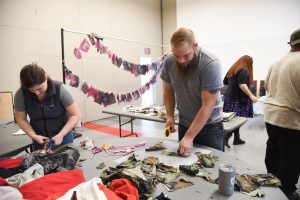 WSU Tri-Cities veteran student Zachary Hays cuts up an old military uniform as part of a process to commemorate his years of service in the U.S. Navy.