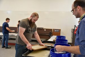 WSU Tri-Cities student Zachary Hays sifts pulp from fabrics to turn it into paper