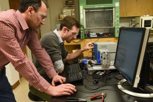 Engineering professor Amir Ameli and graduate student alumnus Josef Christ test 3D-printed sensors made from nanomaterials