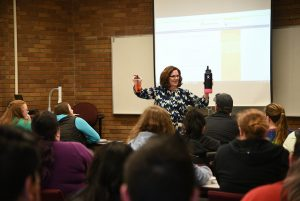WSU Tri-Cities education adjunct professor Cathie Tate holds up two different beverages as part of an illustration for teaching a mathematics concept to young students.