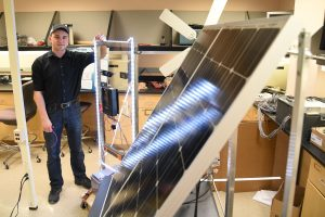 WSU Tri-Cities electrical engineering student Arthur Baranovskiy stands by the solar panels and electrical system designed by him and his fellow student engineers as part of an engineering capstone project