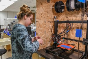 Student Mikaela Matkowski works with a 3D printer as part of her Chancellor's Summer Scholars project