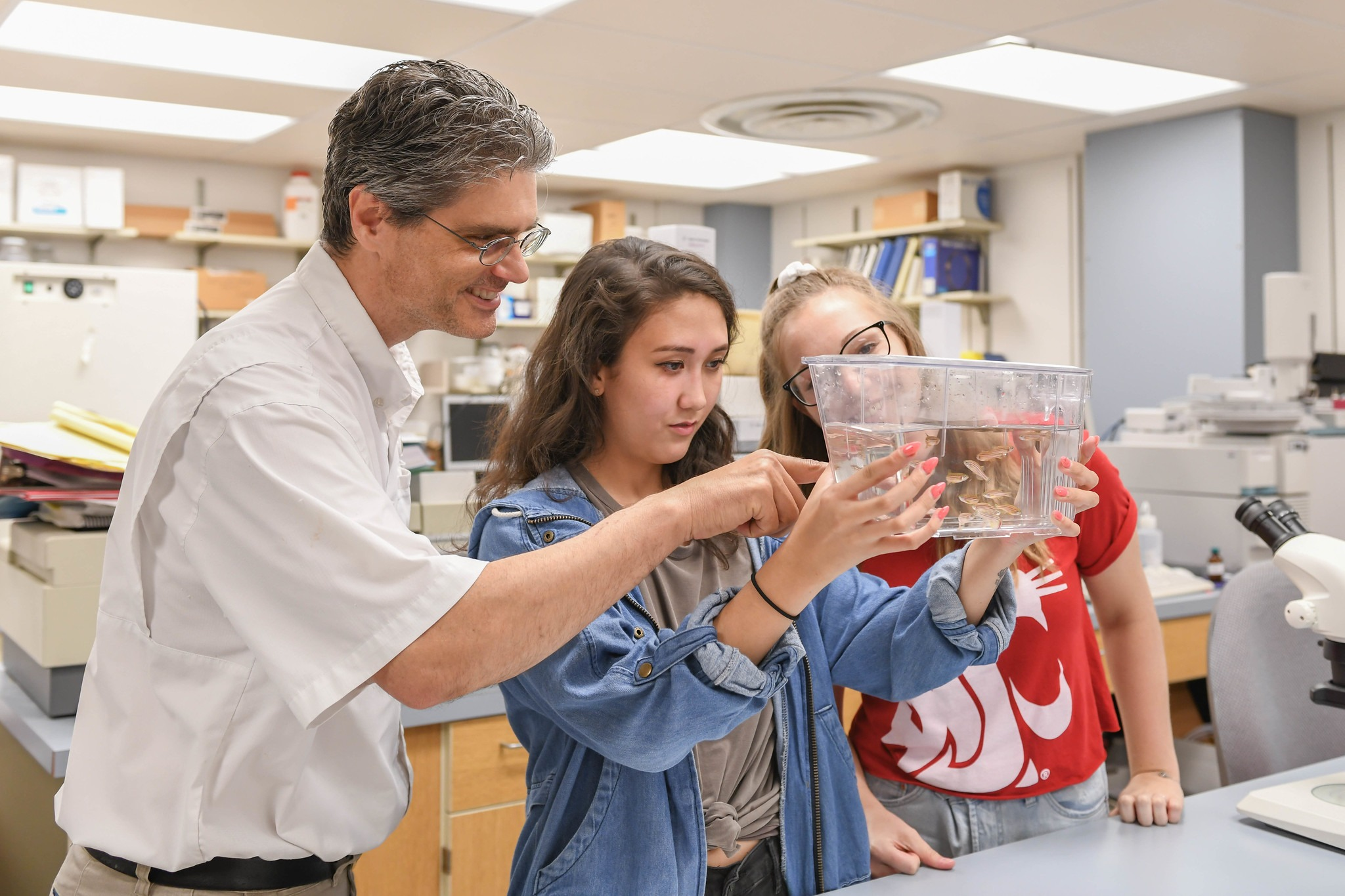 Students Ellie Barber and Danielle Ringo work with Jim Cooper, instructor of biology, in Cooper's fish laboratory as part of their Chancellor's Summer Scholars experience.