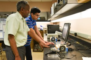 Student Arturo Guttierrez Larios works with Mohamed Osman, professor of electrical engineering, in an engineering laboratory as part of his Chancellor's Summer Scholars experience.