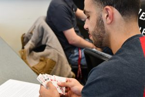 A WSU Tri-Cities student looks through his hand of cards, deciphering instructions for how to play the card game in his English class