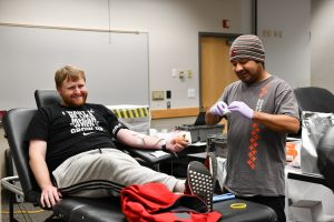 RJ Aubert, WSU Tri-Cities recreation coordinator, gives blood while chatting with his phlebotomist, a WSU Pullman alumnus.