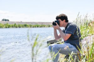 Kyle Kopta, WSU Tri-Cities digital technology and culture alumnus, takes a photo along the river at the WSU Tri-Cities campus