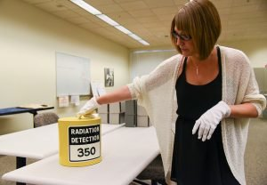 a-wsu-tri-cities-staff-member-examines-an-artifact-from-the-hanford-collection
