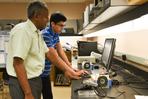 Mohamed Osman works with student Arturo Gutierrez Larios to identify ways to increase the efficiency of several home heating and cooling systems