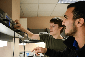 Two electrical engineering students using equipment