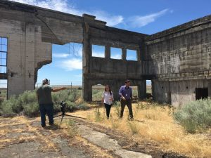 """Robert Franklin (right), assistant director of the WSU Tri-Cities Hanford History Project and teaching assistant professor of history, chats with Sara Cassin (center), a student from Delta High School, at the old Hanford High School on the Hanford Nuclear Reservation as part of a video shoot for the Daytime Emmy-nominated film """"The Manhattan Project Electronic Field Trip."""""""