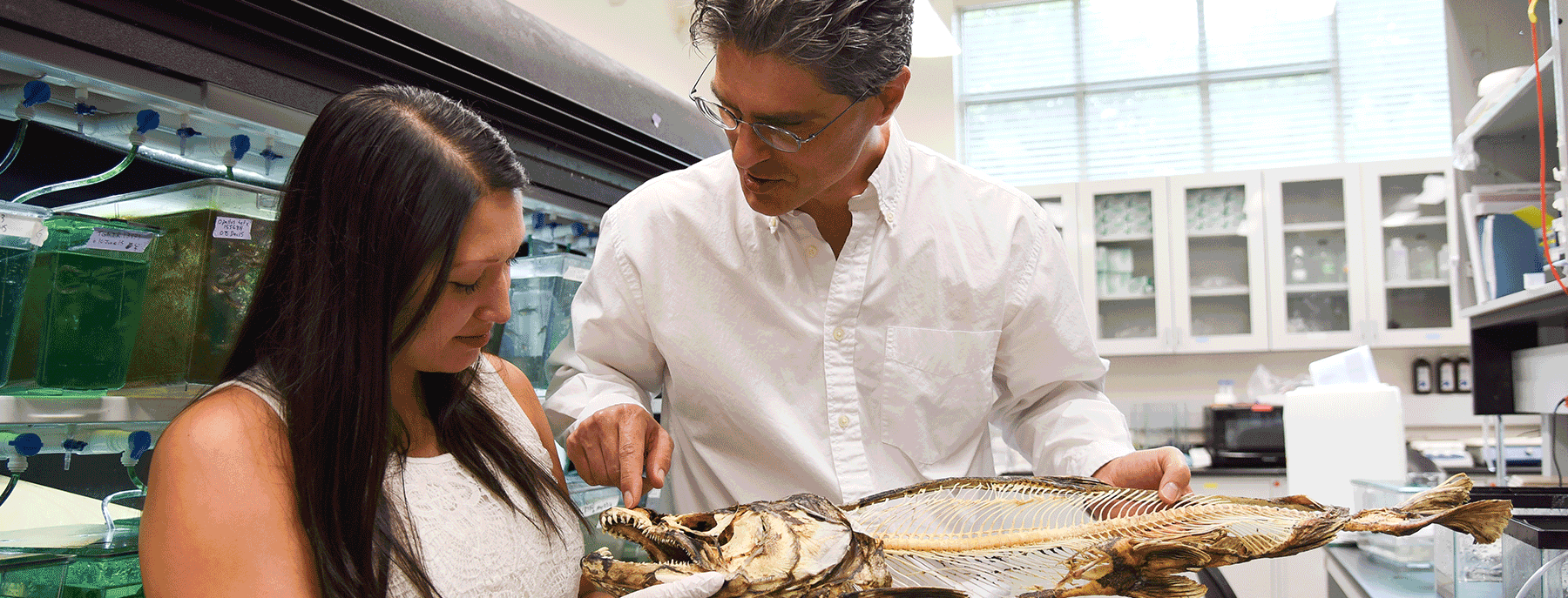 student with professor with a fish skeleton