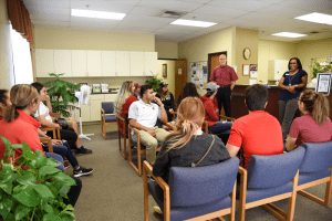 Group of students sit and listen to presentation at health clinic