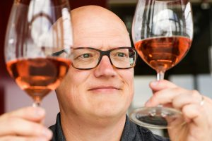 Jim Harbertson examines rose wine in a glass