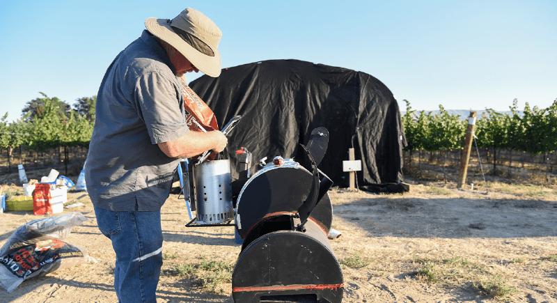 Tom Collins, WSU Tri-Cities wine science professor, sets up an experiment for a smoke trial to analyze the effect of wildfire smoke on wine grapes