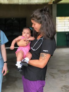 Kenzie McNeel holds an infant while completing her a clinical rotation at a remote village in Peru.