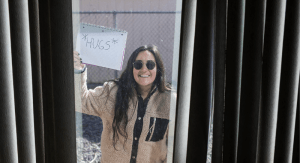 "Carina León holds a sign outside of a window as Madison Rosenbaum takes her photo as part of her ""Tales from Home"" photo series amid COVID-19"