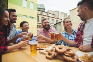 A group of friends enjoying and drinking beer at outdoor bar